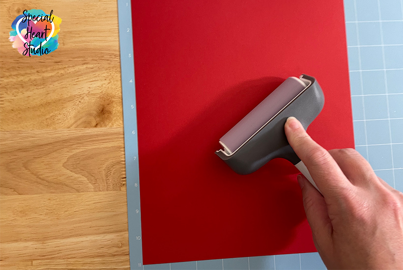 Use a brayer to firmly attach red paper to Criut Mat
