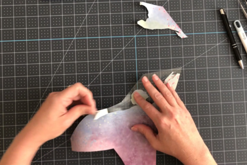 Removing excess Infusible Ink material on a desk.  Also known as weeding the design.
