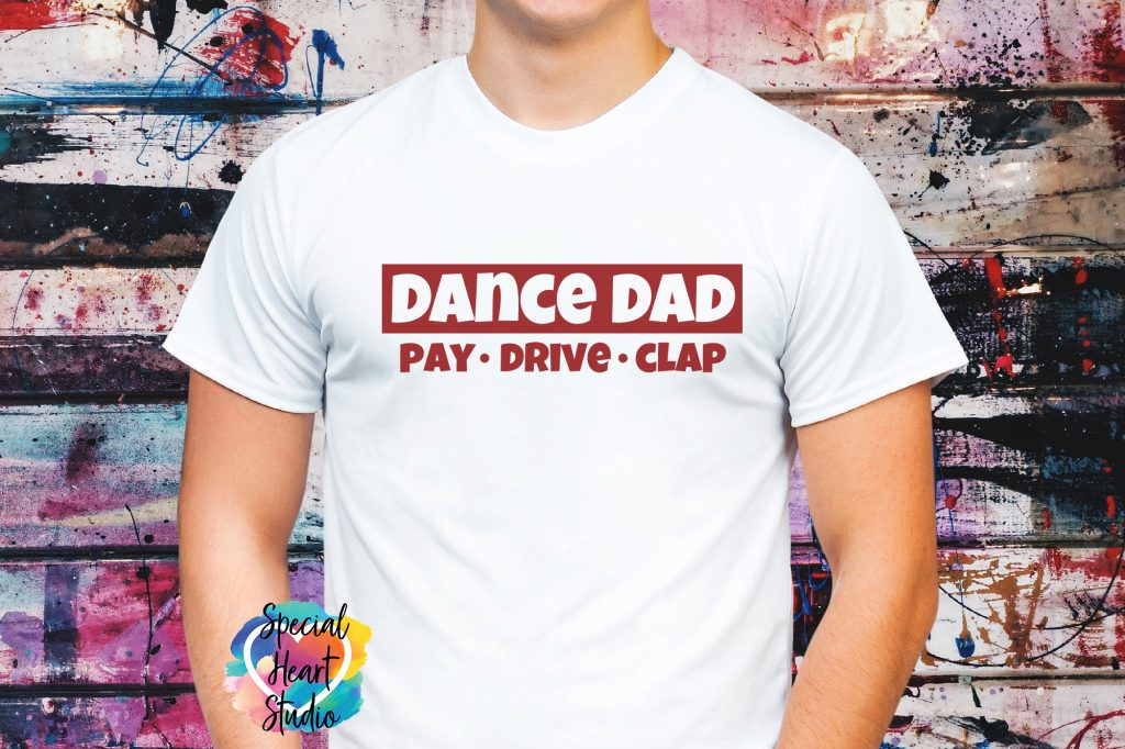 Man's chest wearing white t-shirt with graphic saying Dance Dad. Pay, Drive, Clap