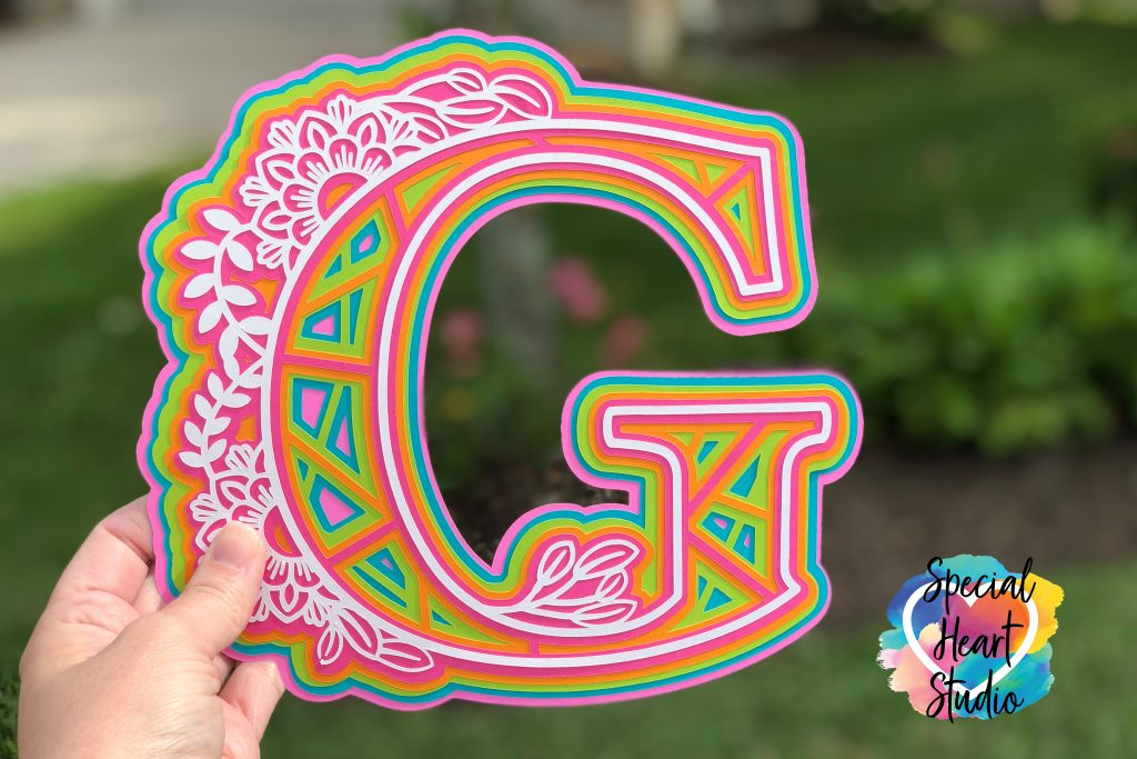 Brightly colored cardstock with letter G cut in a 3D floral mandala style pattern