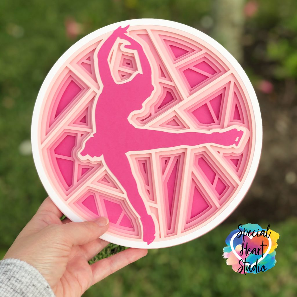 Layers of pink cardstock stacked in a circle with a female figure skater silhouette image