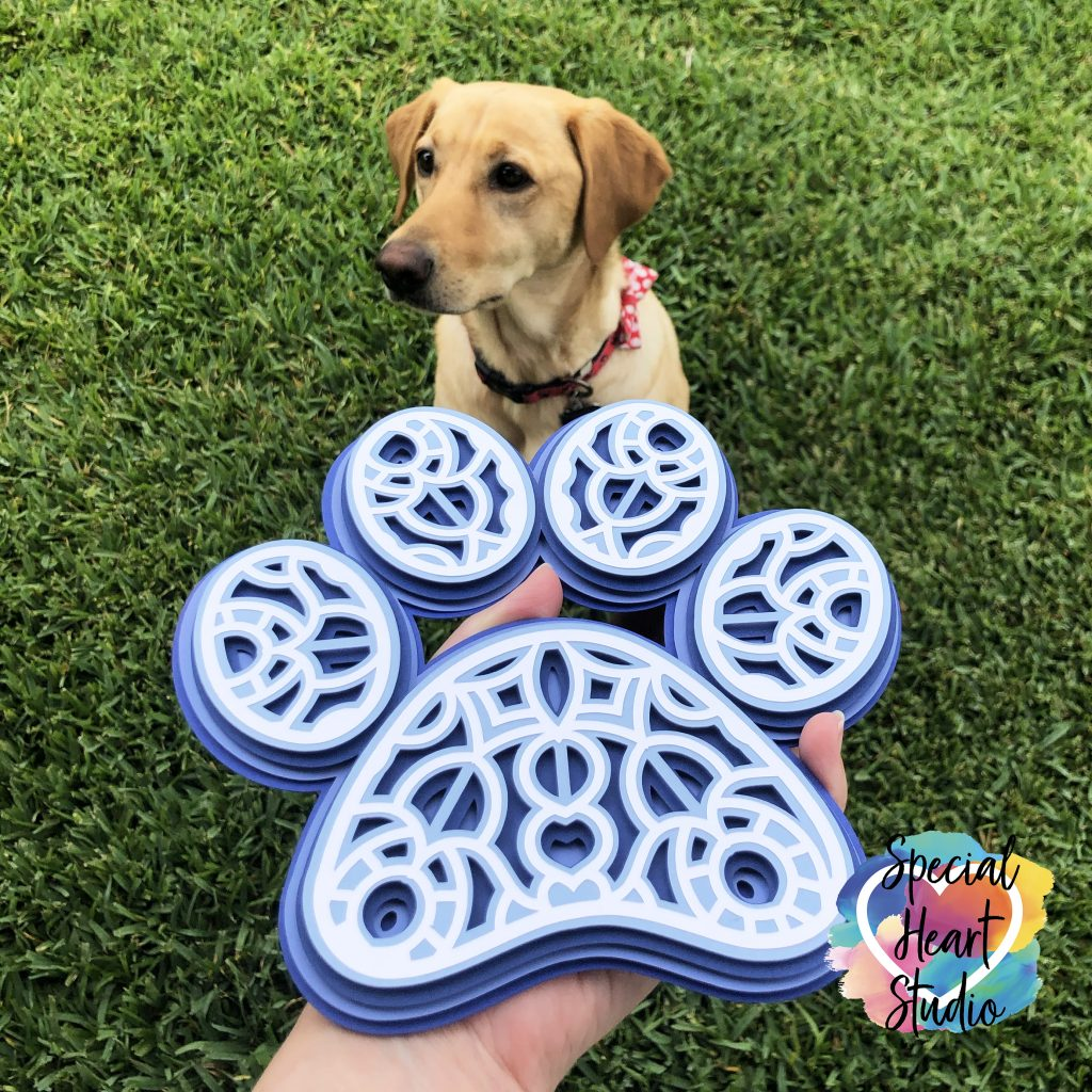 Layered cardstock paw print mandala in blue and white with yellow lab in background in grass