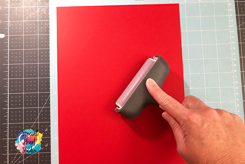 Using a Cricut Brayer to adhere red cardstock to the cutting mat.