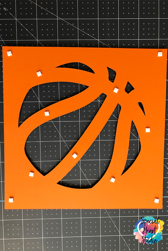 Back side of one layer of basketball cut on a cricut. Foam tab placement.