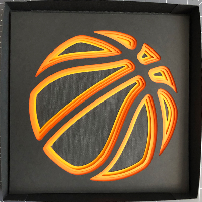 Partially assembled shadow box of layered basketball.
