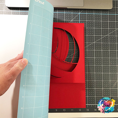 Removing freshly cut cardstock from the Cricut cutting mat.