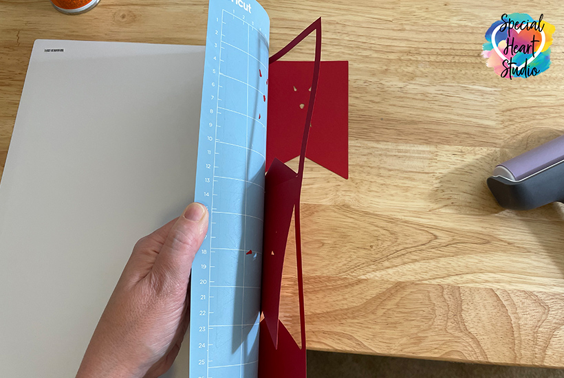 Remove paper from Cricut mat by turning upside down and gently bend mat away from paper