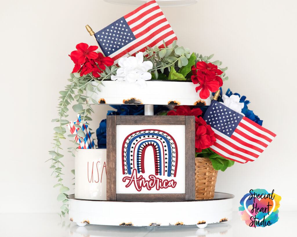 Two tier tray with wood sign in the middle. Sign has boho rainbow in red white and blue with the word America below.  Also on the tray are flowers, greenery and two small US flags.