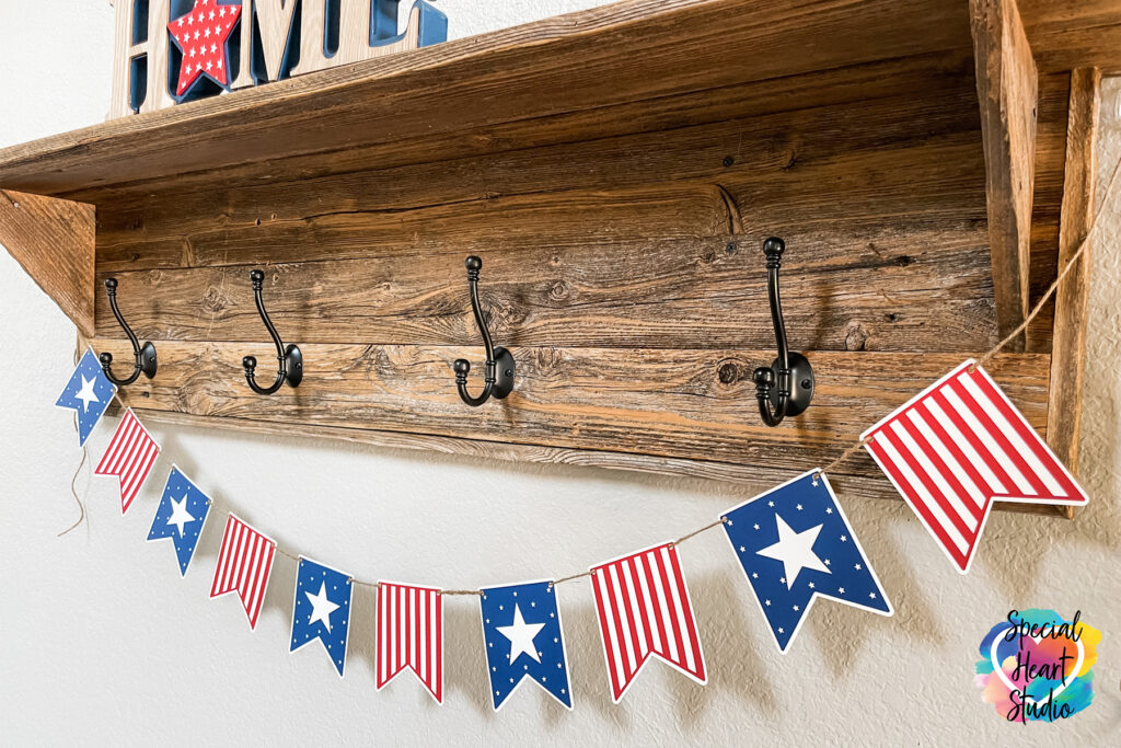 Wood shelf with hooks and hanging from it is a pennant banner.  Every other banner is red & white stripe or has a White background with blue and white stars.