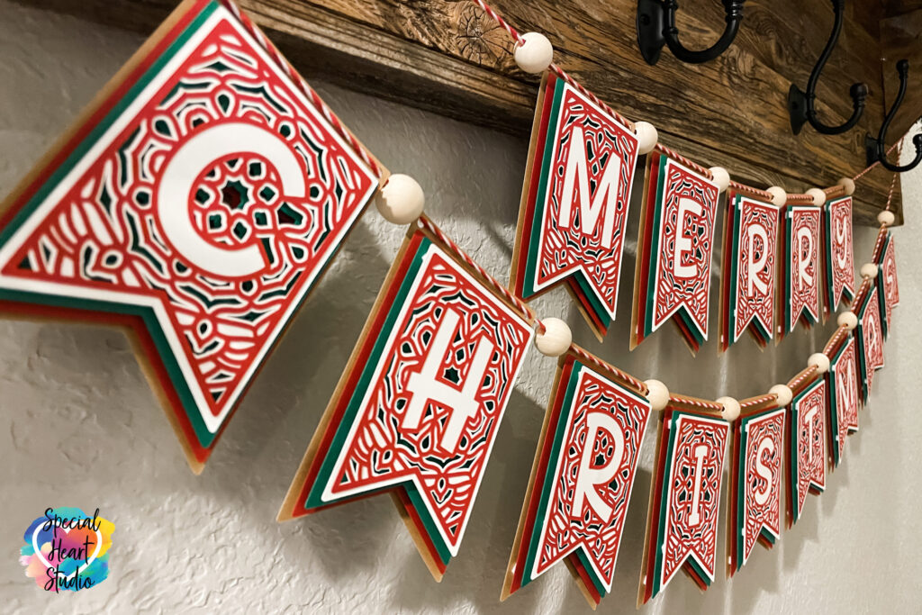 Close up of Layered Merry Christmas Banner with twine and wood beads.