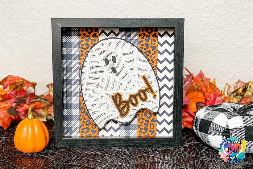 Black square shadowbox frame with layered mandala ghost cut from layers of cardstock with boo! on top.  Printed background.