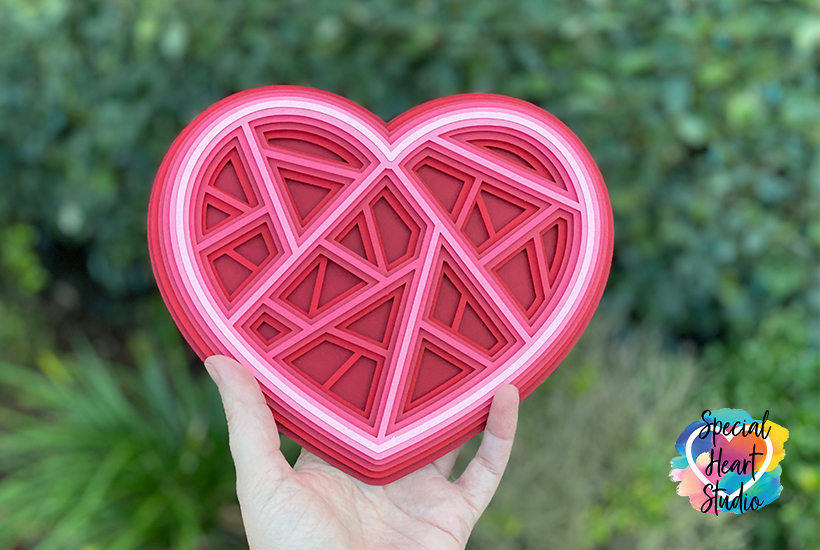 Layered Geometric Heart cut from cardstock in shades of red and pink.