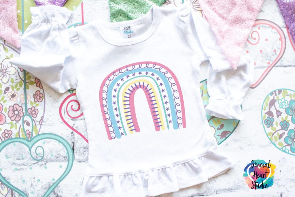 Toddler size white ruffle shirt on pastel baby blanket.  The shirt has a pastel boho rainbow.