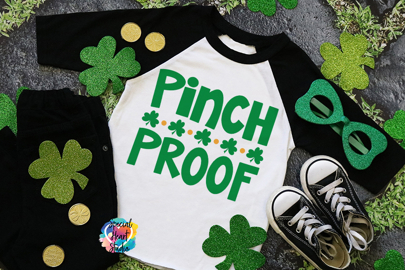Pinch Proof raglan shirt with black arms and green writing.