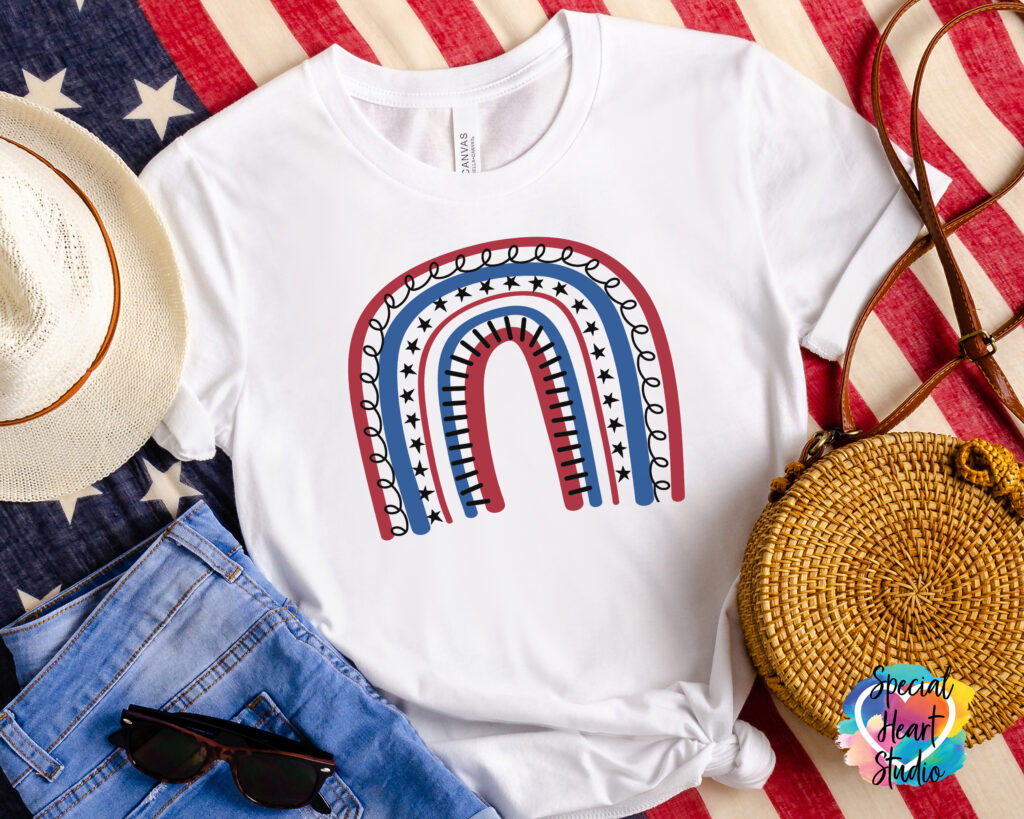 White t-shirt with red, white, and blue rainbow on a flag.  Also in photo jeans, sunglasses a straw hat and purse.