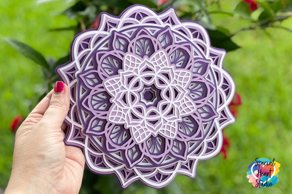 Intricate layered mandala made from purple and white cardstock held outside in front of green grass.