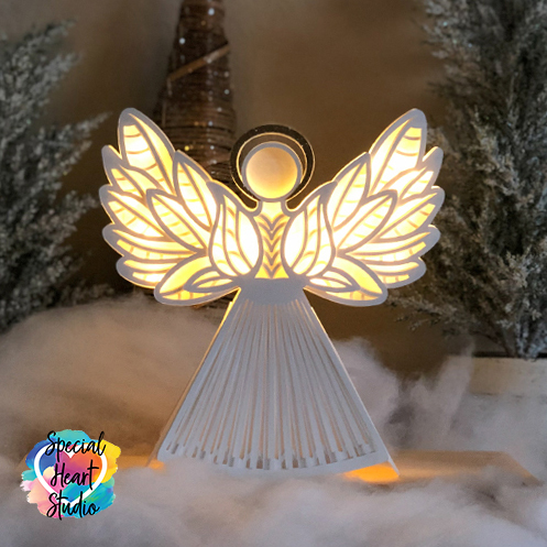 3D white Papercut Angel with wings lit from behind.