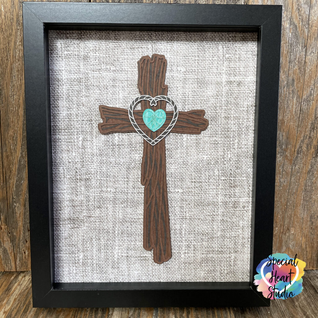 Cross made from cardstock that looks like wood in an 8x10 frame with a turquoise heart.