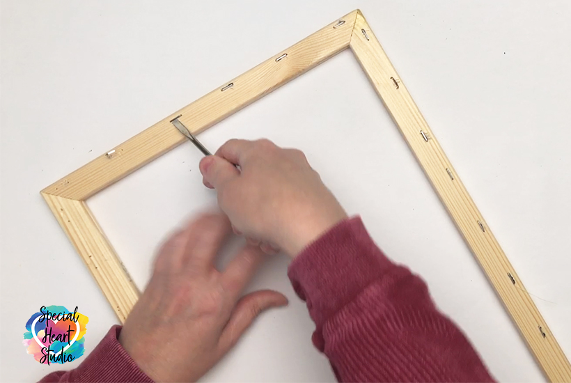 Removing staples from wood frame using flat screwdriver.