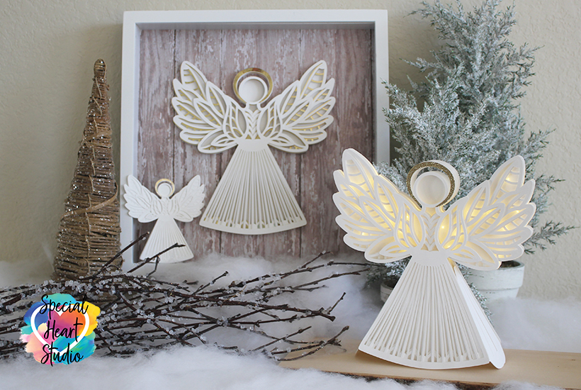 Framed papercut angel from white cardstock with wood background. Another freestanding 3D papercut angel with wings illuminated from fairylights.