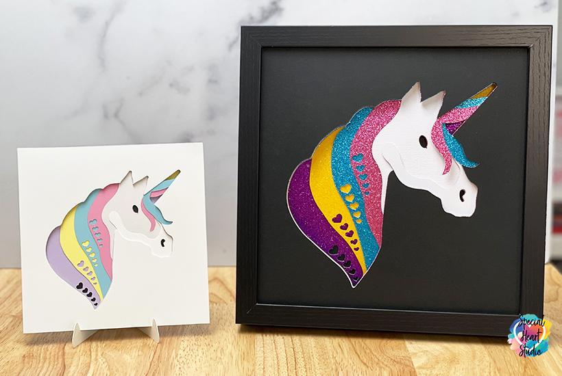 Large framed glitter unicorn shadow box in black frame.