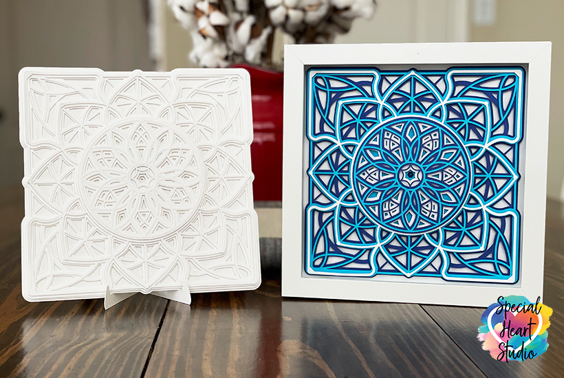 Two layered square mandalas.  There is a plain white mandala and the same pattern in blues and white in a shadowbox frame.